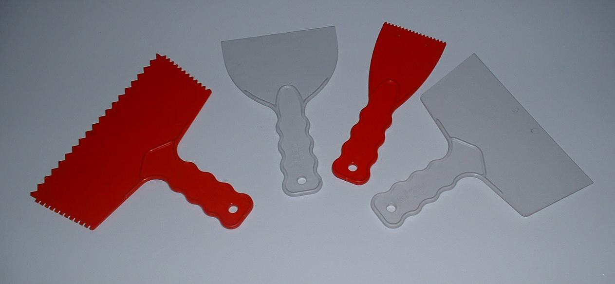 4 Spachteln aus Plastik, 2 x rot mit Zähnen, 2 x grau glatt